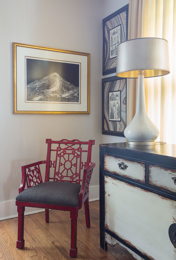 Red decorative corner chair with custom artwork, an antique dresser and white lamp
