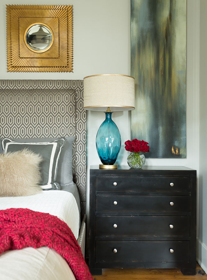 Black end table with blue vase-style lamp, fresh red flowers, a custom watercolor canvas, printed headboard and furry pillow