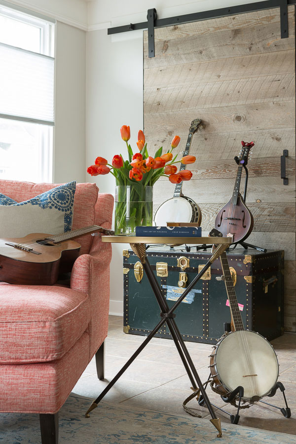 Music focused family room. Colorful chair, end table with flowers, custom artwork and two stringed instruments on display.