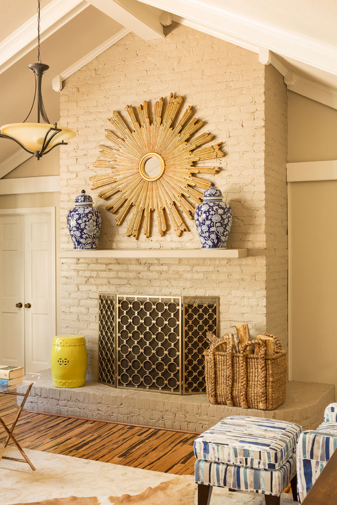 whitewashed fireplace with vases on a mantle and custom wood art
