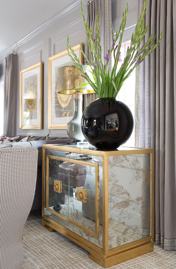 Living room glass and gold accent table with round black vase and fresh flowers