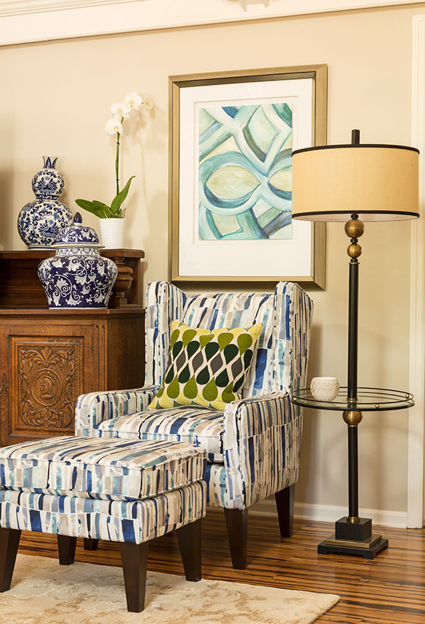 Living room chair in the corner with floor lamp, decorative framed artwork and blue vases