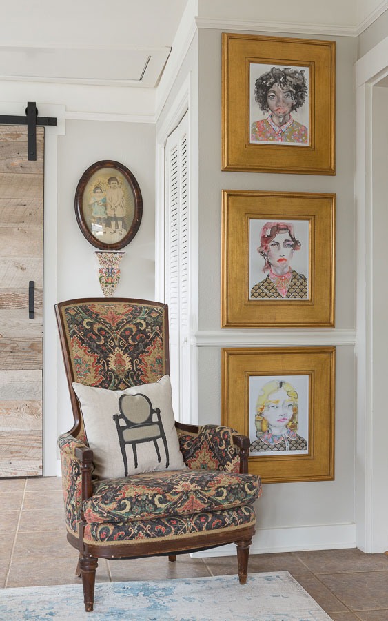 Antique carpet chair with wooden legs next to a wall of portraits
