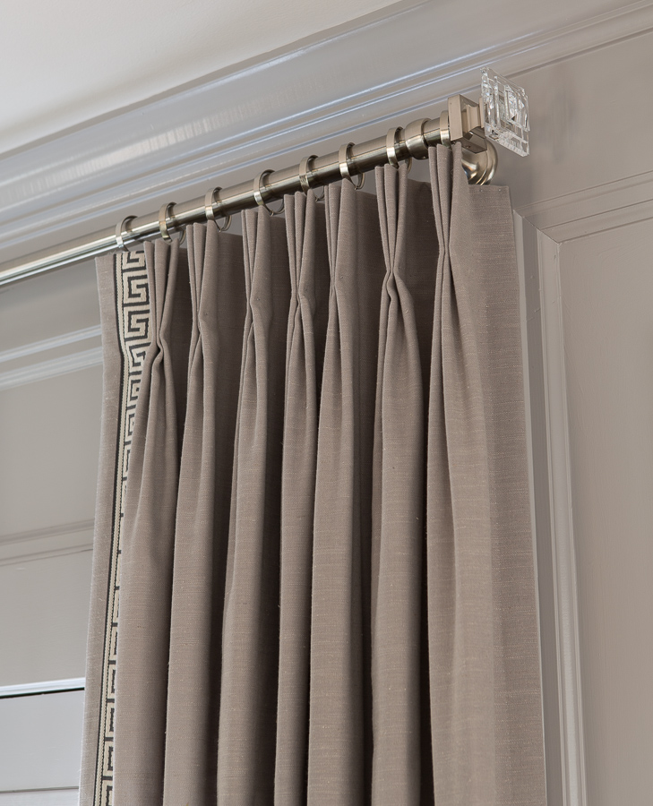 Grey curtain detail with silver curtain rod and crystal trim