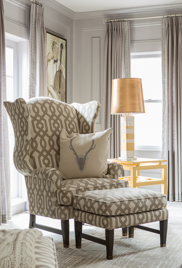 Grey and white accent chair with ottoman beside a yellow end table with a golden and white lamp